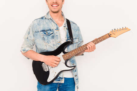 instrumentalist: Close up of young rocker with beaming smile and electric guitar Stock Photo
