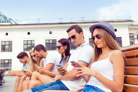 glases: successful young  boyfriends and girlfriends in glases  using their smartphone at summertime