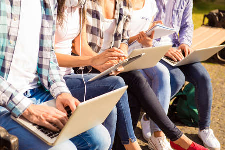 classmates: close-up photo of happy diverse classmates sitting on bench and study up with device Stock Photo