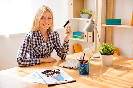 Portrait of happy young woman holding bank card and doing internet shopping