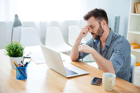 way of thinking: Overworked young man thinking about way to complete task Stock Photo
