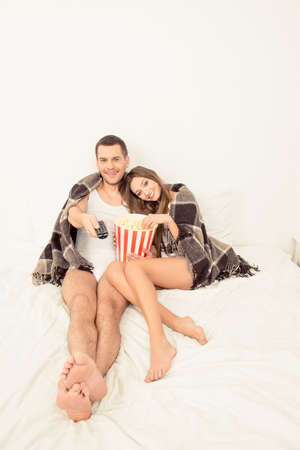 Man and woman in love watching film with popcorn in bed