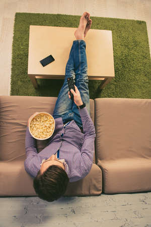 barefoot man: Top view of barefoot man watching tv with popcorn