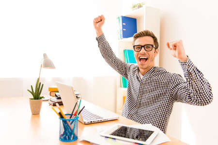 Portrait of happy successful young worker with raised hands