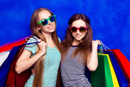 Portrait of two beautiful women in glasses with colorful paperbags Stock Photo