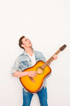 instrumentalist: Portrait of young cool man plaing on the guitar and singing