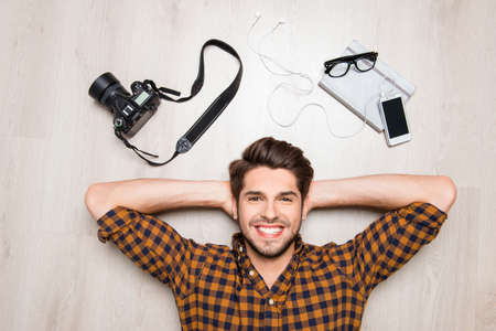 Top view of cheerful happy man lying on floor with camera, glasses and smartphone Stock Photo