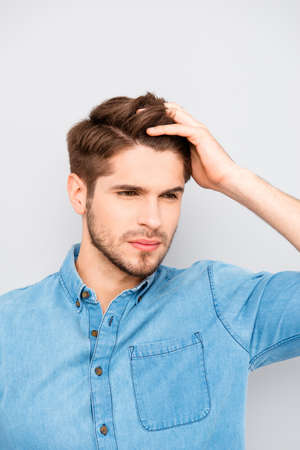 Handsome man touching his hair isolated on gray background Stock Photo