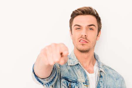 怒っている若い男のカメラで彼の指を指しているジーンズのジャケットで 写真素材