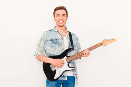 Portrait of happy young man playing on electric guitar