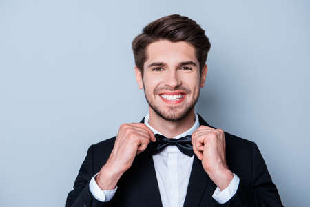 beaming: Cheerful handsome man with beaming smile corecting his bow tie Stock Photo