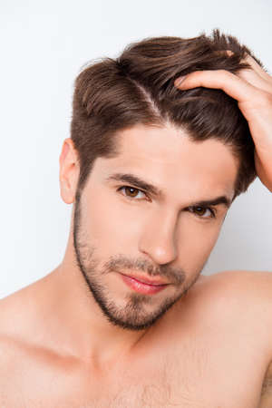 combining: Portrait of handsome bearded man combining his hair Stock Photo