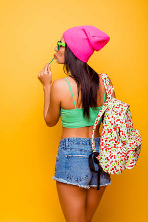 booty shorts: back view of happy  girl with backpack and lollipop, standing yellow background Stock Photo