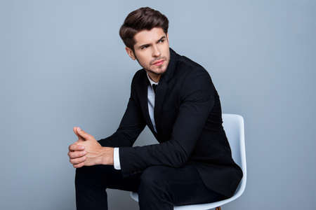 minded: Young minded businessman in black suit sitting on chair
