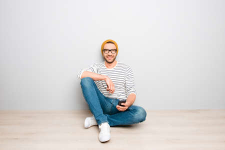 sms: Handsome hipster man in yellow cap and glasses typing sms