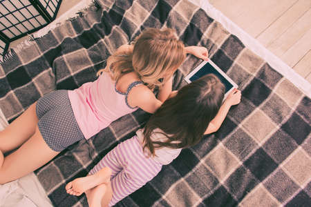 Top view of of small daughter and mother lying on bed with tablet Stock Photo