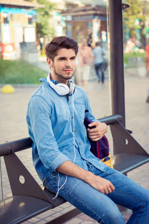 handsome young man sitting bus stop and waiting Stock Photo