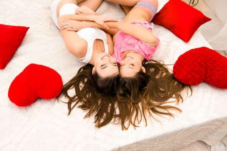 pijamada: Vista superior de muchachas de risa en pijama acostado en la cama y huging Foto de archivo