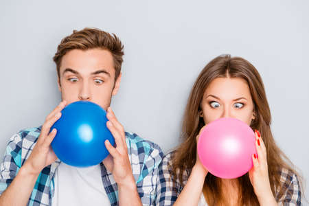 inflating: Portrait of funny happy young man and woman inflating balloons Stock Photo