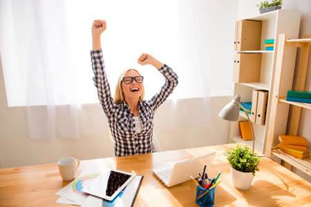 Happy successful woman in glasses achiving goal in her  office