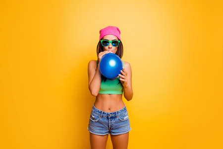 inflate: Happy funny hipster girl in pink hat inflate balloon near yellow wall