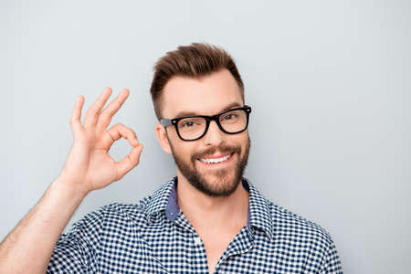 isolated on gray: Cheerful young man in spectacles showing OK gesture