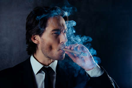 smoking a cigar: portrait of brutal handsome man with stubble smoking a cigar Stock Photo