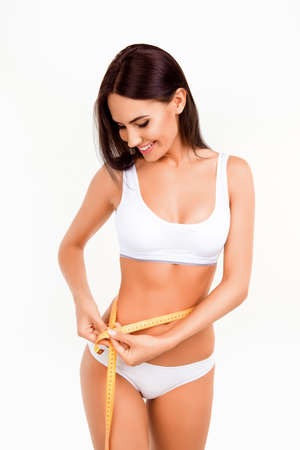 Portrait of beautiful fit slim woman measuring her waist Stock Photo - 61771038