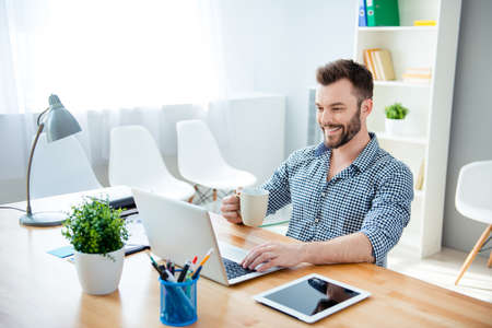 everyday jobs: Young  happy businessman  drinking coffee while working on laptop