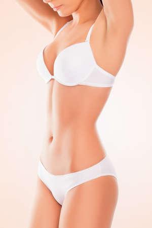 mujer celulitis: Cerrar una foto del cuerpo de la mujer delgada en ropa interior blanca aislada en el fondo de color rosa Foto de archivo