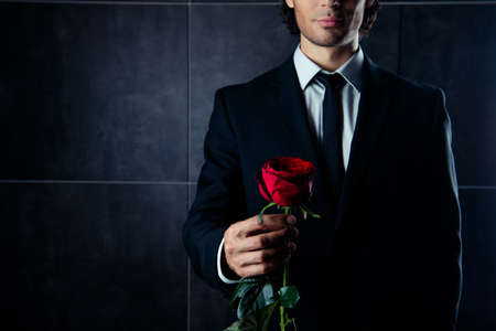 Closeup photo of handsome  young man in formalwear  holding red rose Stock Photo