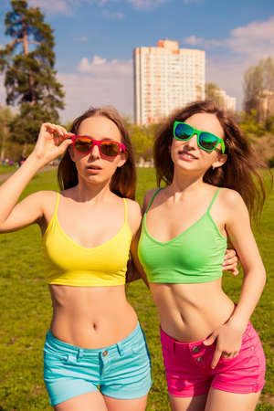 Two happy fit women in glasses showing their slim bellies