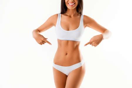 그녀의 슬림 근육질 배꼽을 가리키는 웃는 여자의 닫습니다