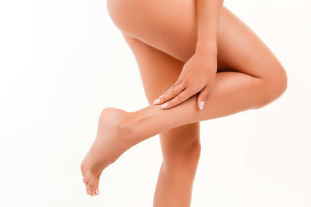 Young woman massaging her healthy legs, close up photo
