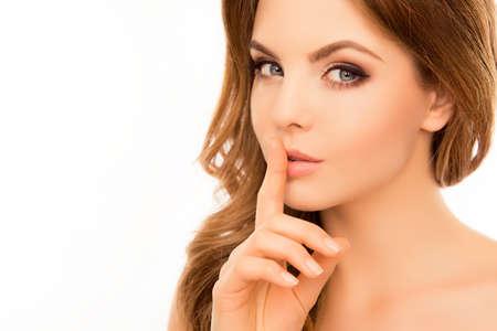Hübsche Frau mit Geheimnis und Finger halten auf Lippen Standard-Bild