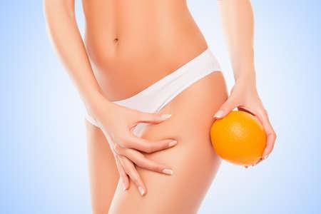 white panties: Woman in white panties holding orange near hip and checking fat on leg