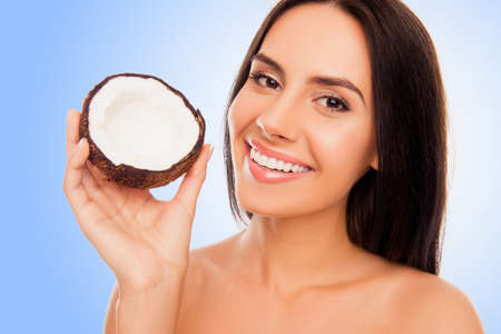 lift hands: Portrait of young woman with beaming smile holding half of coconut in hand Stock Photo