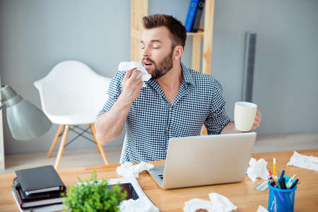 rheum: Sick businessman holding cup of hot tea and sneezing in tissue