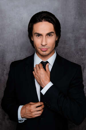 correcting: Portrait of confident young man  correcting his black  tie