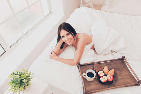 breackfast: Happy girl in bed with wooden tray with tasty breackfast