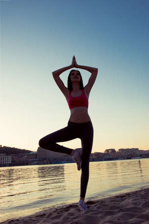 Portrait of young healthy woman practising yoga on sunset Stock Photo