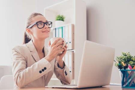 everyday jobs: Minded woman in glasses dreaming with cup of coffee during her break Stock Photo