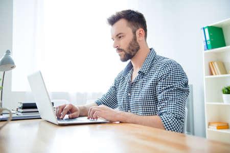 Zijaanzicht van geconcentreerde man schriftelijk boek over laptop Stockfoto