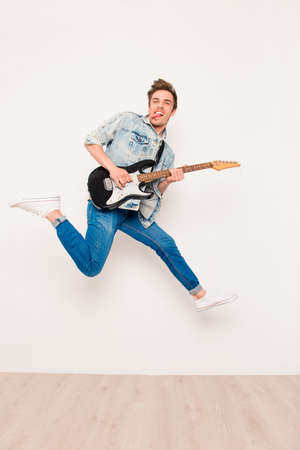 instrumentalist: Young man playing on electric guitar, showing tongue and jumping Stock Photo