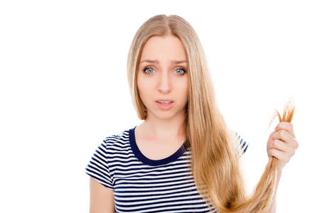 Sad girl looking at her damaged hair