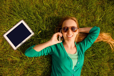 sward: Smiling girl lying on lawn with tablet and talking on phone Stock Photo