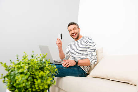 Happy man doing internet shopping and holding credit card