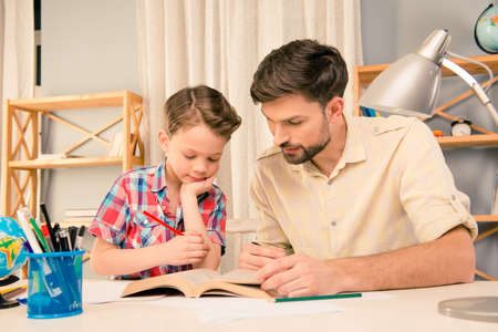 Father and his little son studing with interesting book