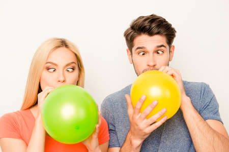 Two funny lovers inflating balloons for celebration and grimacing Stock Photo