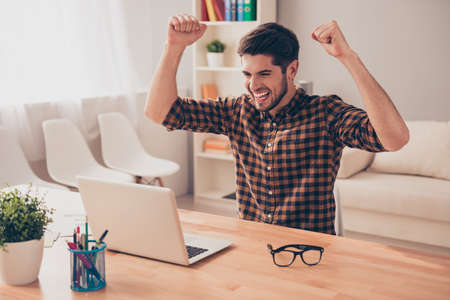 Happy businessman successfuly completed his task and triumphing with raised hands
